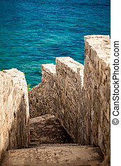 ancient stone wall with stairs leading to blue sea