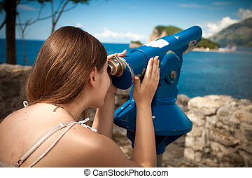 young woman looking on mountain through touristic telescope