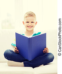 smiling little boy reading book on couch - leisure,...