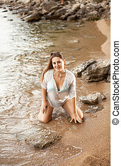 sexy woman in shirt kneeling on sandy beach - Portrait of...