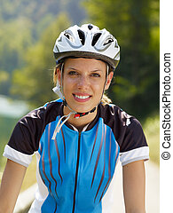 female cyclist - young woman with bicycle helmet, looking at...