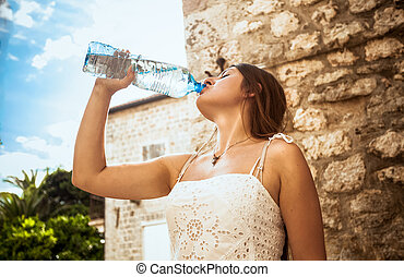 young woman drinking water out of plastic bottle on street -...