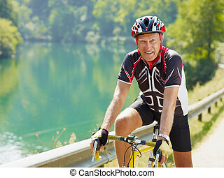 senior cyclist - senior man on road bike, looking at camera....