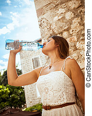 young brunette woman drinking water out of bottle at sunny...