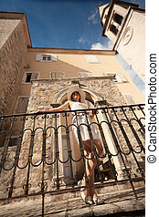 young woman leaning against metal railings on old stone...