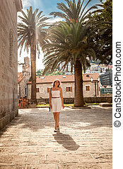 woman walking on street with ancient building and high palms...