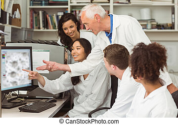 Science students looking at microscopic image on computer...