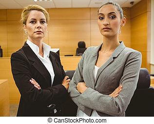 Two serious lawyers standing with arms crossed in the court...