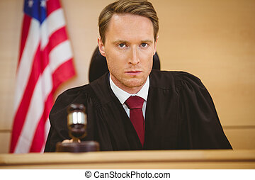 Portrait of a judge about to bang gavel on sounding block in...