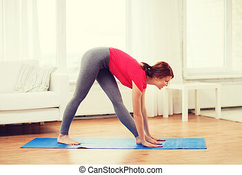 smiling teenage girl streching at home - fitness, home and...