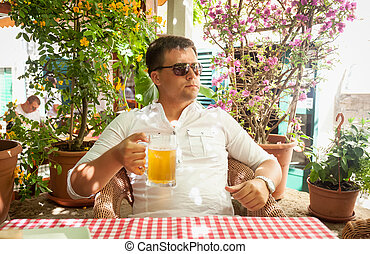 young man drinking beer at restaurant - Portrait of young...