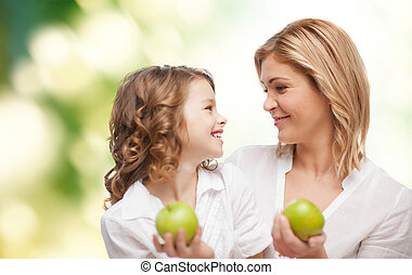 happy mother and daughter with green apples - people,...