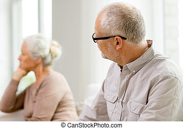 senior couple sitting on sofa at home - family, relations,...