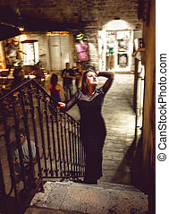 woman in black cocktail dress posing on old stairs at night