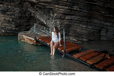 young woman in white shirt sitting in sea cave - Sexy young...