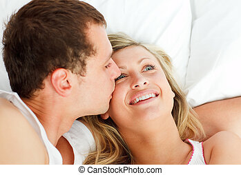 Boyfriend kissing his girlfriend in bed - Close-up of...