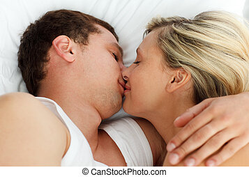 Amorous couple kissing in bed