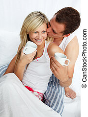 Couple in bed drinking coffee with affection - Couple...