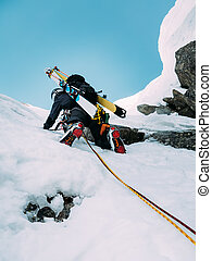 Ice climbing: mountaineer on a mixed route of snow and rock duri