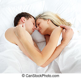 Boyfriend and girlfriend sleeping in bed together