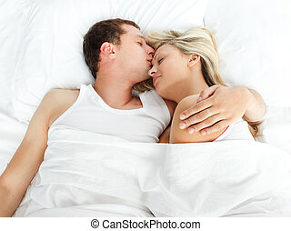 Boyfriend kissing his girlfriend in bed - High view of...