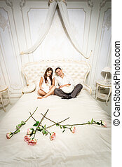 couple in love sitting on luxurious bed decorated with roses...