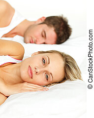 Couple lying in bed and woman looking at the camera