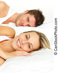 Couple resting in bed and woman smiling at the camera