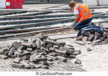 road construction - Worker with protective vest paves the...
