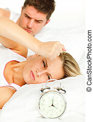 Man and angry woman in bed looking at the alarm clock going off