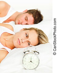 Couple in bed and angry woman looking at the alarm clock