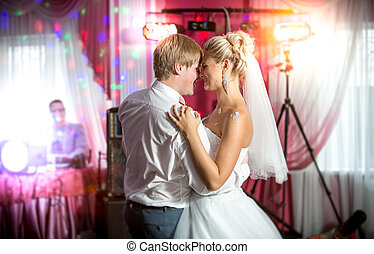 newly married couple dancing at colorful lights and flares -...