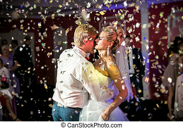 portrait of confetti flying at dancing beautiful bride and...