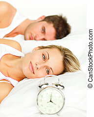 Woman lying with her boyfriend looking at the alarm clock
