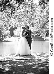full length portrait of kissing bride and groom at park near the