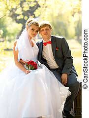 smiling bride and groom sitting on bench at river under big...