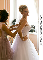 mother assisting bride in putting wedding dress on -...