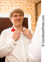 portrait of handsome young man putting on red bow tie -...