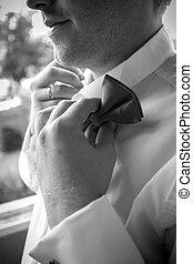 Black and white photo of elegant man adjusting bow tie -...