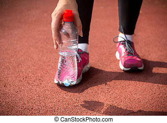 woman runner holding plastic bottle of water on running...