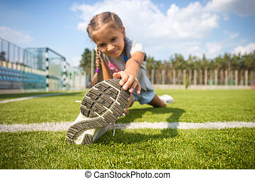 young girl stretching on grass before running - Cute young...