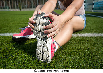 young woman warming up on grass before running - Closeup...