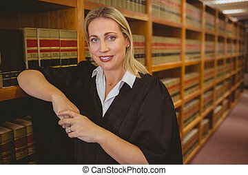 Smiling lawyer leaning on shelf in library