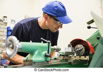 Engineering student using machinery - Engineering student...