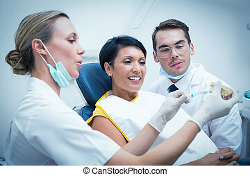 Dentist showing how to brush teeth - Female dentist with...