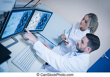 Science students looking at microscopic images at the...