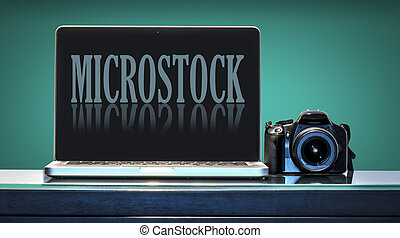 Microstock trend - Laptop and reflex camera over a desk with...