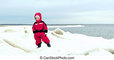 little girl on winter snow-covered coast