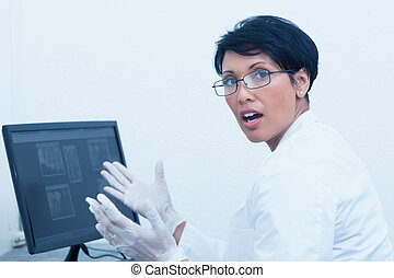 Female dentist with x-ray on computer