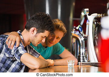Caring friend comforting upset man at the bar
